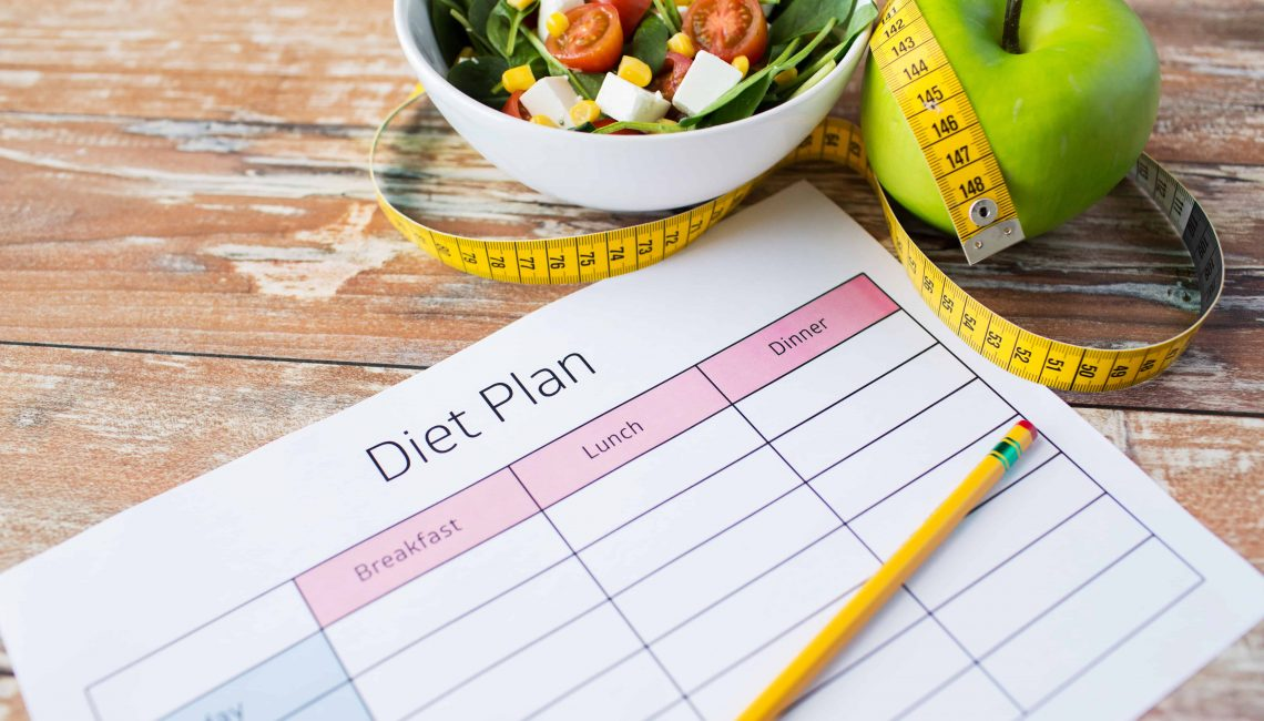 healthy eating, dieting, slimming and weigh loss concept - close up of diet plan paper with green apple, measuring tape and salad